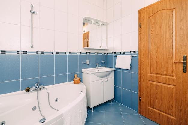 Badezimmer mit hydromassage-badewanne, waschbecken mit spiegel und brauner holztür