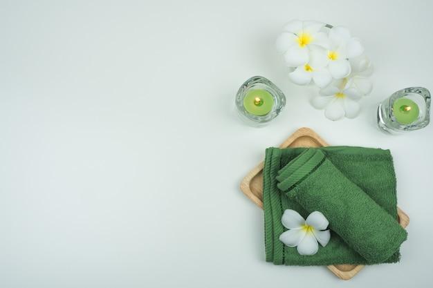 Badezimmer set.spa eingestellt. grünes tuch und kerze mit plumariablume auf der weißen tabelle.