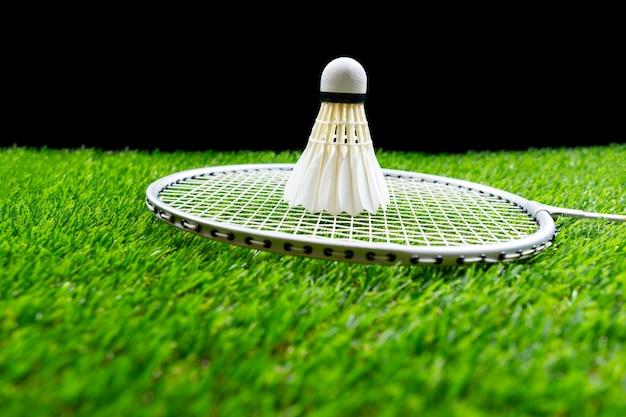 Badmintonball und -schläger auf gras im schwarzen hintergrund