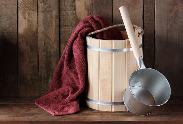 Badutensilien: holzeimer, frotteehandtuch und eimer. dampfbad, sauna.