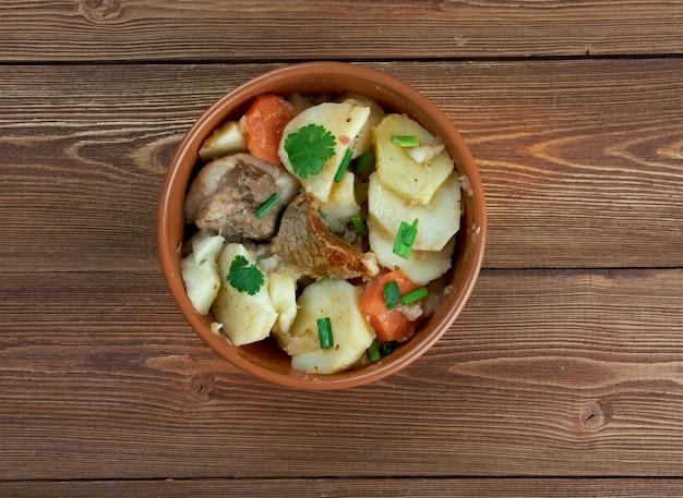 Baeckeoffe - typisches gericht aus frankreich, deutschland. mischung aus geschnittenen kartoffeln, geschnittenen zwiebeln, hammelwürfeln, rind- und schweinefleisch