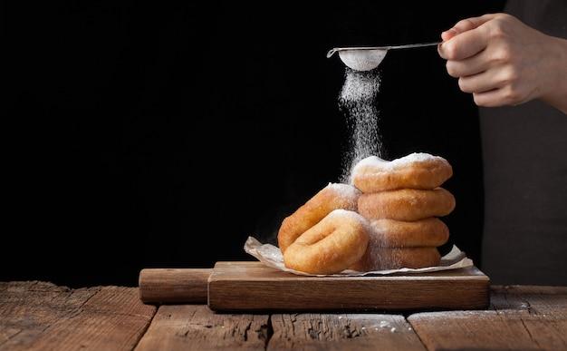 Bäcker besprüht süße donuts mit puderzucker.