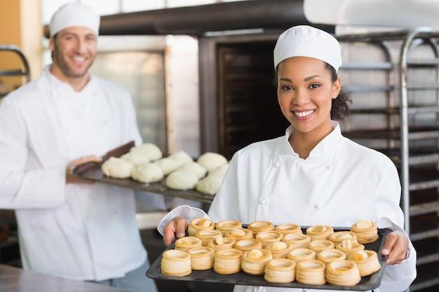 Bäcker, der an der kamera hält behälter lächelt