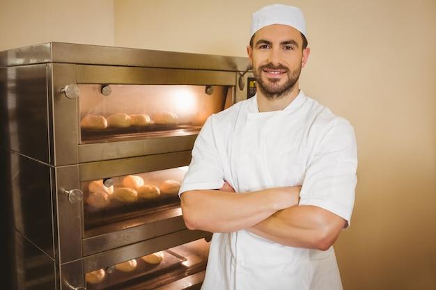 Bäcker, der an der kamera neben ofen lächelt