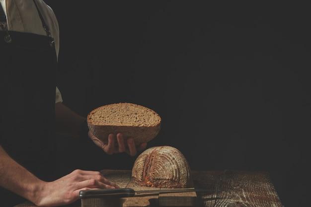 Bäcker, der auf dunklem hintergrund eine hälfte frisch gebackenes brot in der hand hält