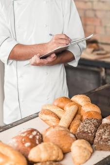 Bäcker, der auf klemmbrett mit vielen broten auf küche worktop schreibt