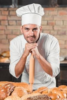 Bäcker, der auf nudelholz über der tabelle mit vielzahl von broten sich lehnt