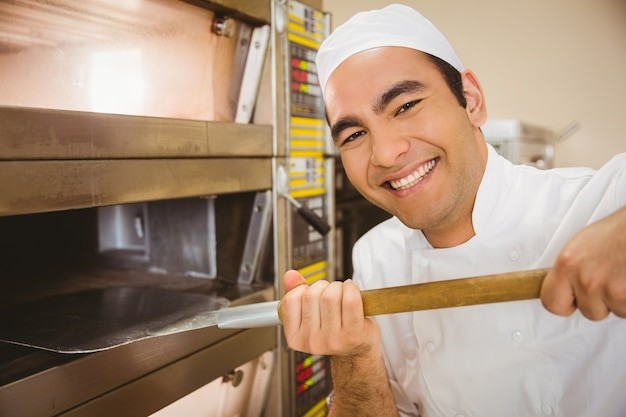 Bäcker, der brot aus ofen heraus nimmt