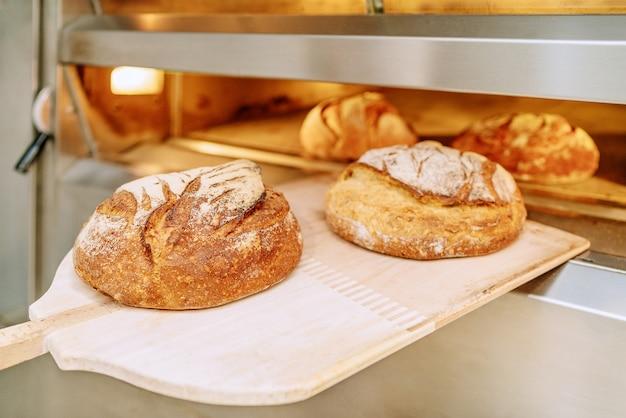 Bäcker, der brot in den backofen legt und auf dem boden der bäckerei kauert
