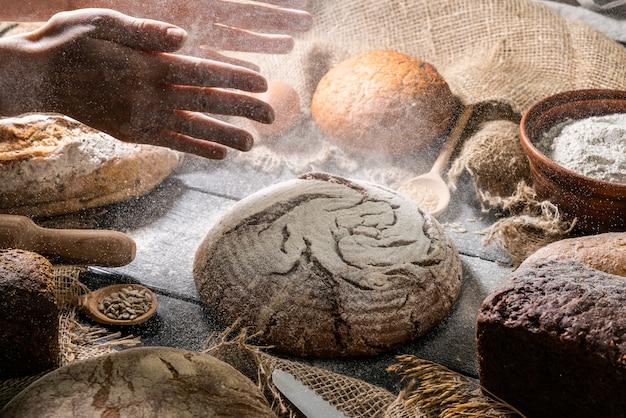 Bäcker, der brot kocht. frau schlägt mehl über den teig.