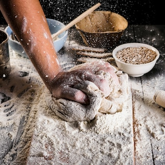 Bäcker, der das weizenmehl auf den teig über dem küchentisch besprüht