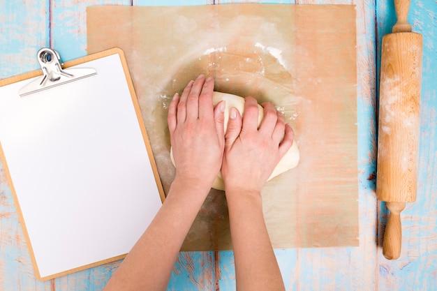 Bäcker, der den teig auf pergamentpapier mit klemmbrett und nudelholz auf tabelle knetet