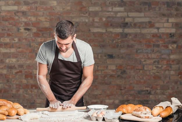 Bäcker, der den teig mit nudelholz auf zähler gegen backsteinmauer flachdrückt