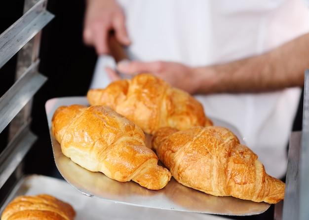 Bäcker, der ein tellersegment mit frisch gebackener nahaufnahme der französischen hörnchen anhält