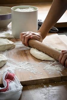 Bäcker, der einen teig in der küchennahaufnahme knetet