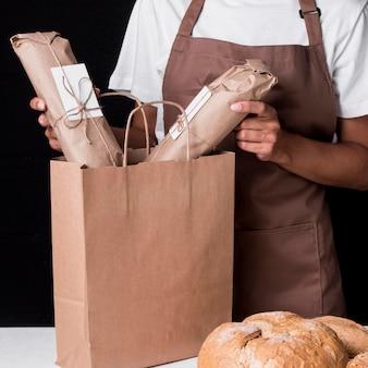 Bäcker, der eingewickeltes brot in papiertüte legt