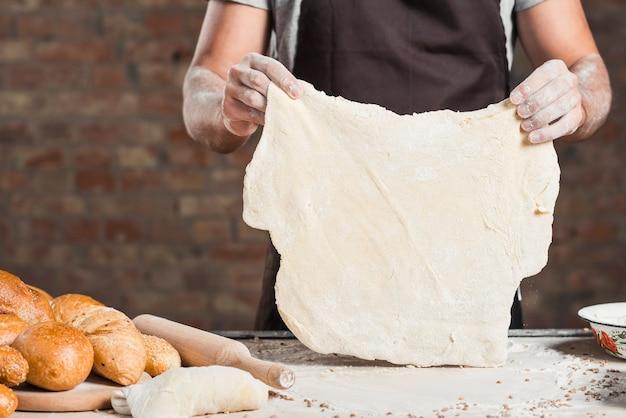 Bäcker, der flach gemachten teig auf küchenarbeitsplatte hält