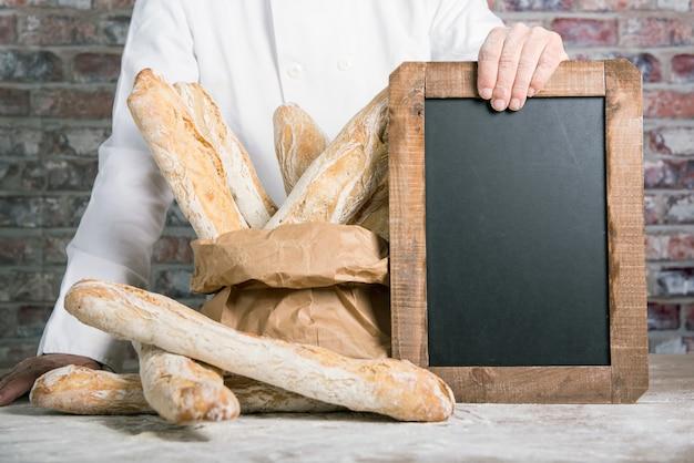 Bäcker, der französische stangenbrote des brotes mit tafel hält