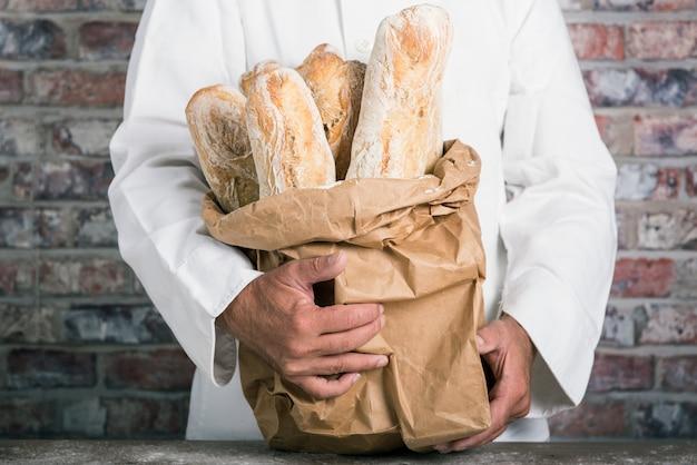 Bäcker, der französische stangenbrote des traditionellen brotes hält