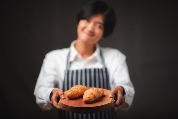 Bäcker, der frisch gebackene croissants im café präsentiert, das vom blätterteig hergestellt wird, der leckeres, französisches bäckereikonzept aussieht.