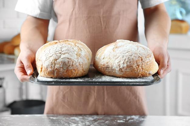 Bäcker, der frisch gebackenes brot in der küche der bäckerei prüft