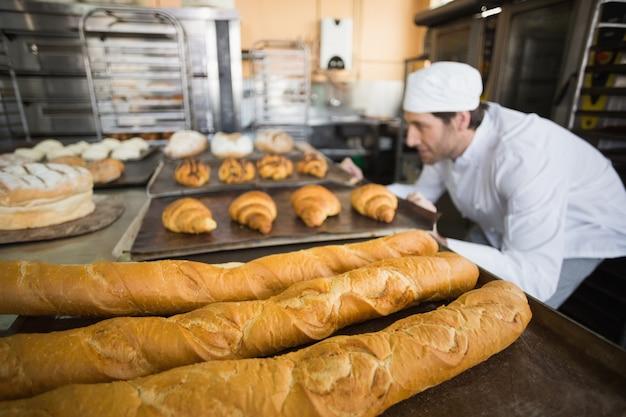 Bäcker, der frisch gebackenes brot überprüft