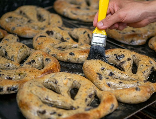 Bäcker, der frisch gebackenes olivenbrot mit olivenöl bürstet