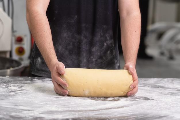 Bäcker, der frischen teig des rohen brotes an der bäckerei knetet.