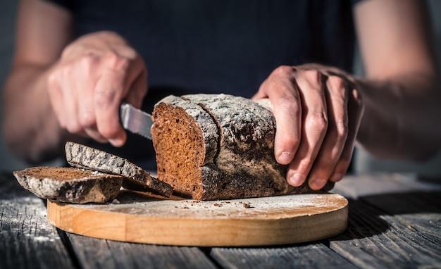 Bäcker, der frisches brot in den händen hält