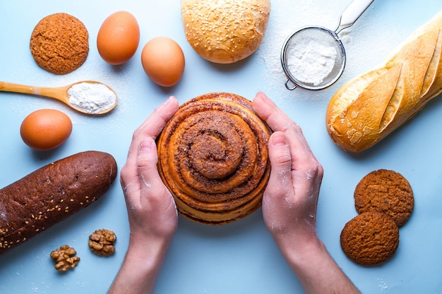 Bäcker, der frisches hausgemachtes zimtbrötchen hält. verschiedene frische, knusprige backwaren und backzutaten
