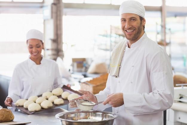 Bäcker, der mehl in eine schüssel sieben