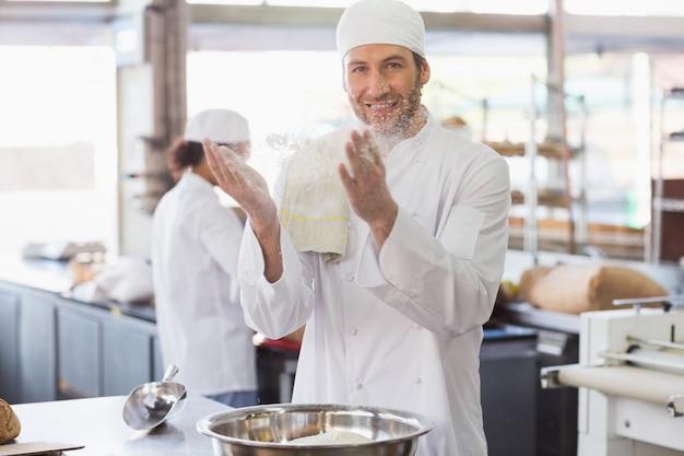 Bäcker, der mehl von seinen händen klatscht