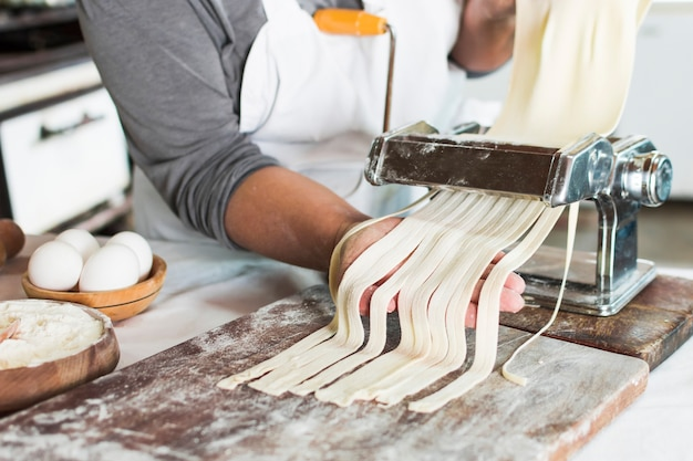 Bäcker, der rohen teig in bandnudeln auf teigwarenmaschine über dem hölzernen brett schneidet