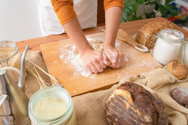 Bäcker, der teig für gebäck auf holzbrett knetet