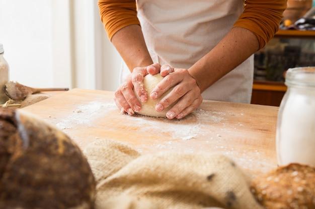 Bäcker, der teig in kugel auf holzbrett bildet