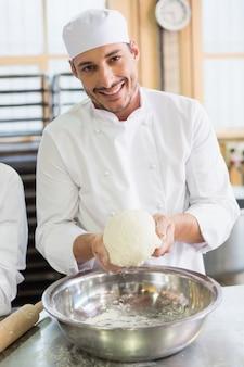 Bäcker, der teig in mischender schüssel bildet