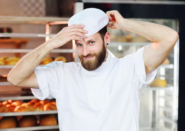 Bäcker des gutaussehenden mannes setzt eine arbeitskappe auf