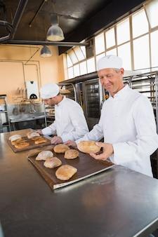 Bäcker, die frisch gebackenes brot überprüfen