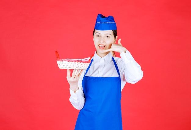 Bäcker in der blauen schürze, die einen brotkorb mit rotem handtuch innen hält und bittet, anzurufen und zu bestellen.