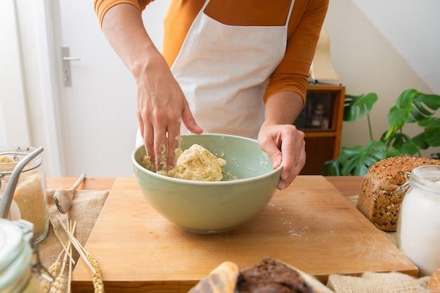 Bäcker in schürze kneten teig für leckeres gebäck und brot