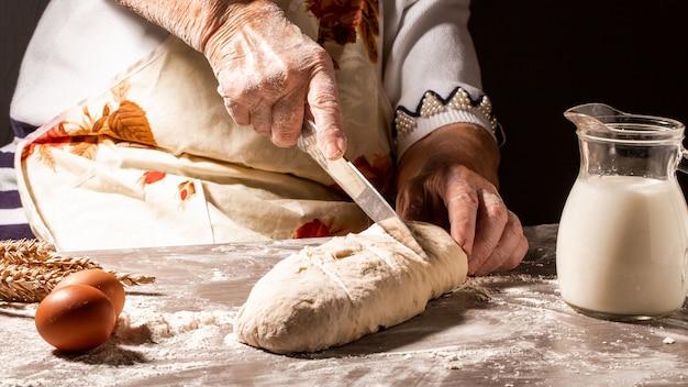 Bäcker machen muster auf rohem brot mit einem messer, um den teig vor dem backen zu formen. herstellungsprozess von spanischem brot. lebensmittelkonzept