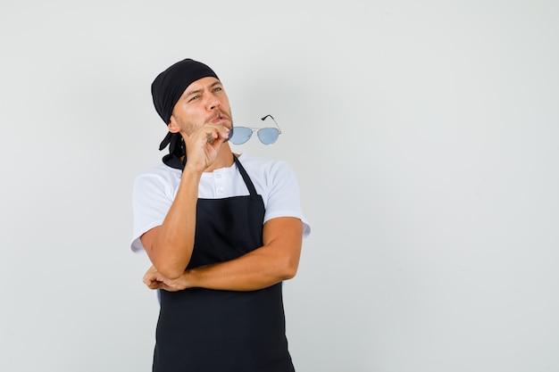 Bäcker-mann, der brille hält, während im t-shirt oben schaut