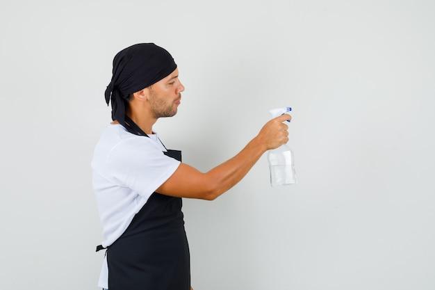 Bäcker mann, der flasche des antiseptischen sprays im t-shirt hält