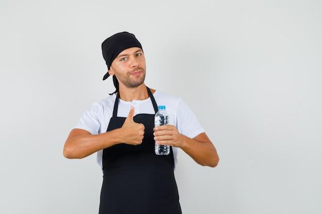 Bäcker mann, der flasche wasser hält, zeigt daumen oben im t-shirt