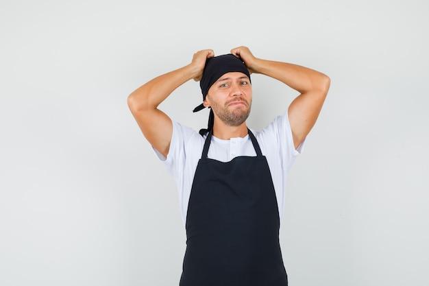 Bäcker mann, der hände auf kopf im t-shirt hält