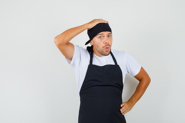 Bäcker mann, der hand auf kopf im t-shirt hält
