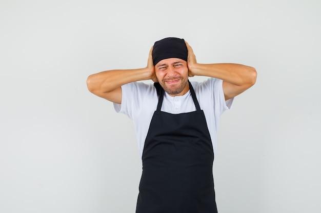 Bäcker mann, der kopf in den händen im t-shirt umklammert