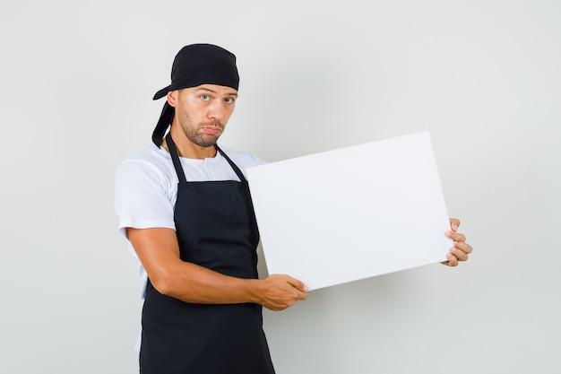Bäcker mann, der leere leinwand im t-shirt hält