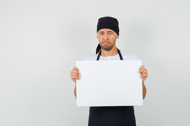 Bäcker mann, der leere leinwand in t-shirt, schürze hält und traurig aussieht.