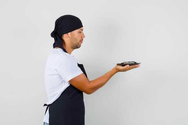 Bäcker mann, der metallisches tablett im t-shirt hält